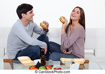 Una pareja comiendo hamburguesas
