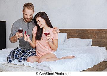 Una pareja comprometida mirando el anillo de diamantes y bebiendo vino