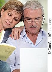 Una pareja con portátil y libro