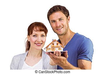 Una pareja con una casa de modelos
