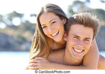 Una pareja con una sonrisa perfecta posando en la playa