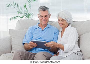 Una pareja con una tabla sentada en el sofá