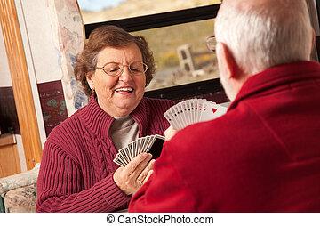 Una pareja de adultos jugando a las cartas en su remolque