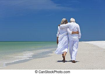 Una pareja de ancianos caminando sola en una playa tropical