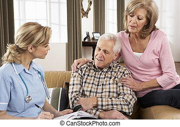 Una pareja de ancianos hablando con un visitante en casa