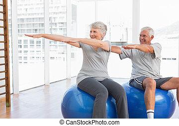 Una pareja de ancianos haciendo ejercicios de estiramiento en pelotas de fitness