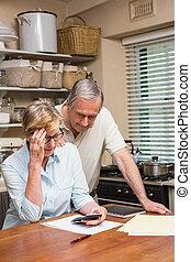 Una pareja de ancianos trabajando en sus cuentas
