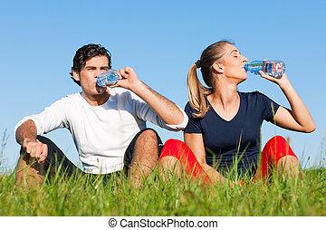 Una pareja de bromistas descansando y bebiendo agua