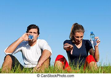 Una pareja de corredores descansando y bebiendo agua