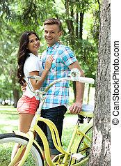 Una pareja de enamorados con bicicleta. Alegre pareja de enamorados de pie junto al otro y apoyado en la bicicleta