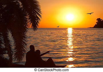 Una pareja de enamorados mirando hermoso atardecer en la costa del mar