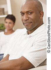 Una pareja de hombres americanos felices sentados en casa