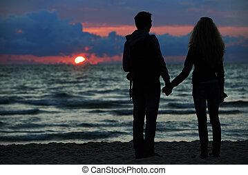 Una pareja de jóvenes en la playa del atardecer