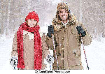 Una pareja de jóvenes esquiando juntos