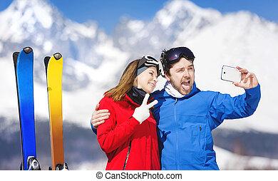 Una pareja de jóvenes esquiando