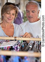 Una pareja de mediana edad comprando ropa.