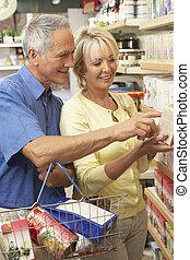 Una pareja de mediana edad comprando té de hierbas