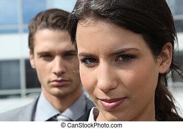 Una pareja de negocios fuera de un edificio de oficinas