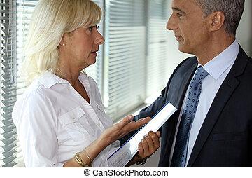 Una pareja de negocios mayor hablando en una oficina