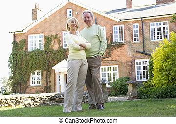 Una pareja de pie fuera de su casa