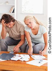 Una pareja desgastada calculando sus gastos