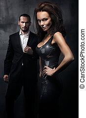Una pareja elegante en un cuarto oscuro