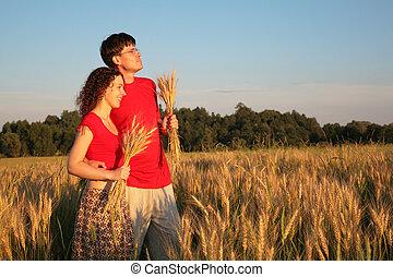 Una pareja en el campo con trigo en las manos