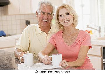 Una pareja en la cocina con café sonriendo
