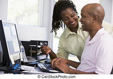 Una pareja en la oficina con tarjeta de crédito usando computadora y smilin
