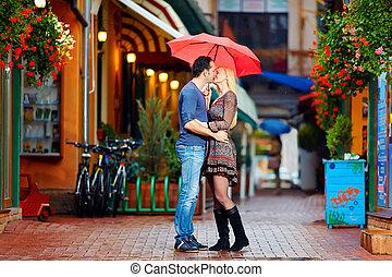 Una pareja enamorada besándose bajo la lluvia