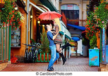 Una pareja enamorada divirtiéndose bajo la lluvia