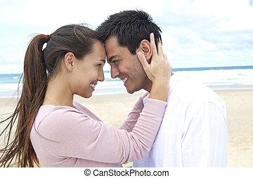 Una pareja enamorada en la playa coqueteando