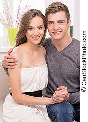 Una pareja encantadora en casa. Hermosa pareja joven abrazando y sonriendo mientras se sientan en el sofá