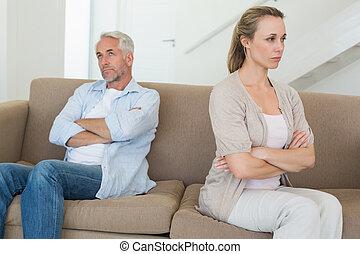 Una pareja enfadada sentada en el sofá sin hablarse