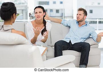 Una pareja enojada hablando con su terapeuta