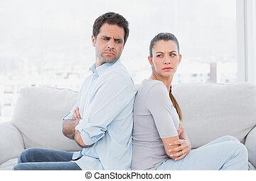 Una pareja enojada sentada en el sofá