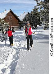 Una pareja esquiando en su chalet