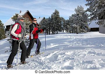 Una pareja esquiando por chalets