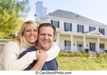 Una pareja feliz abrazándose en frente de la casa