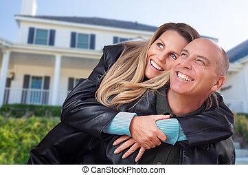 Una pareja feliz abrazándose frente a una hermosa casa