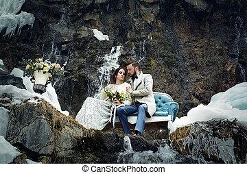 Una pareja feliz abrazada en roca en el fondo de la naturaleza