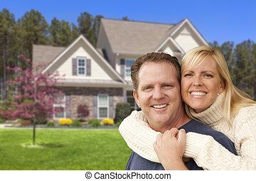Una pareja feliz abrazada frente a casa
