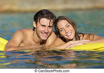 Una pareja feliz bañándose en la playa en vacaciones de verano