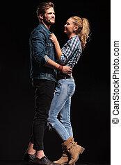 Una pareja feliz berreándose y abrazándose