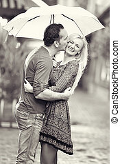 Una pareja feliz besándose bajo la lluvia