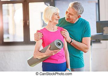 Una pareja feliz con colchoneta de yoga en clase de gimnasia