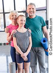 Una pareja feliz con colchonetas de yoga y una chica sonriente de pie juntos en la clase de gimnasia