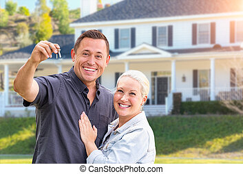 Una pareja feliz con llaves nuevas en la casa hermosa