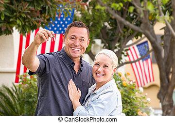 Una pareja feliz con llaves nuevas frente a casas con banderas americanas