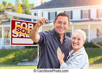 Una pareja feliz con llaves nuevas frente a una firma de bienes raíces vendidas y una hermosa casa
